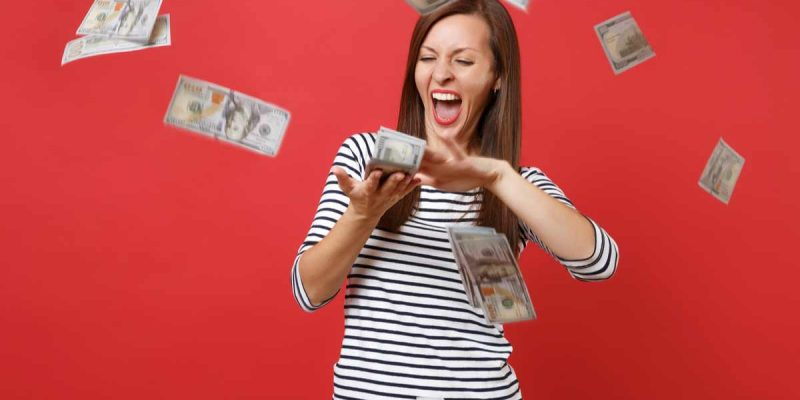 Woman with money blowing out of her hands