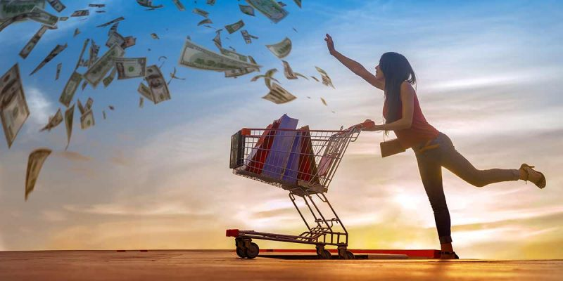 Woman with grocery cart chasing dollar bills