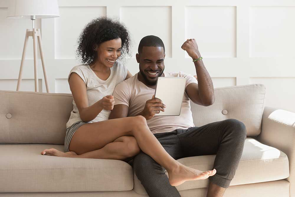 Young couple on a laptop celebrating good news
